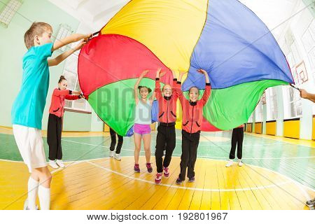 Group of happy 11-12 years old boys and girls playing parachute games in sports hall