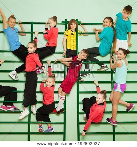 Big group of happy preteen boys and girls in sweatsuits exercising on the bars of wall-mounted gym ladder
