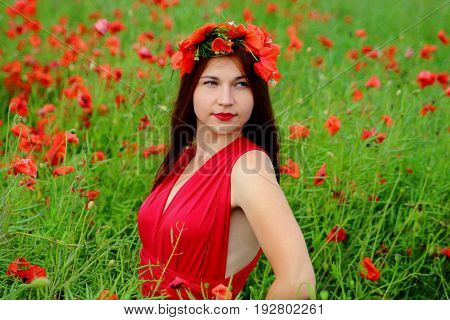 Girl in a poppy field with a wreath in red dress