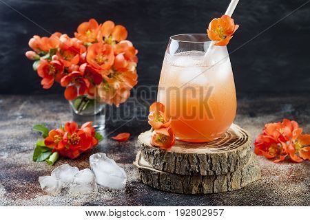 Floral pastel peach and pink brunch cocktail garnished with quince flowers over old rustic background.