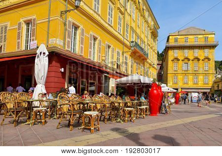 NICE, FRANCE - JUNE 4, 2017: A view of the ambiance and a typical French cafe in the Charles Felix Square in the center of the Vielle Ville, the Old Town, of this popular city in the French Riviera
