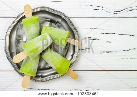 Detox healthy green smoothie popsicles. White wooden rustic background overhead top view flat lay copy space