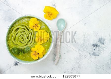 Breakfast detox green smoothie bowl topped with kiwi rose and edible Pansy flowers. Overhead top view flat lay copy space