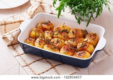 Roasted potatoes with garlic thyme and rosemary in ceramic baking dish