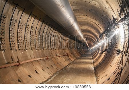 Empty tunnel under construction for the metro. Large temporary ventilation pipe under the ceiling subway tunnel