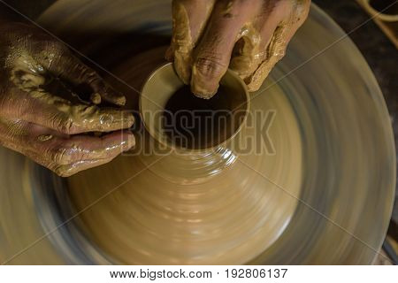 creative hands  making clay pot on the molding wheel.