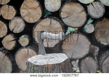 A Deck Of Stacked Logs And An Axe