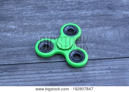 Green fidget spinner stress relieving toy on wooden background.