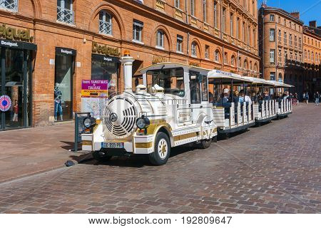 Toulouse France - March 26 2017 : Train touris on the streets in the Capitole de Toulouse Facade of the Capitol the City Hall of Toulouse France