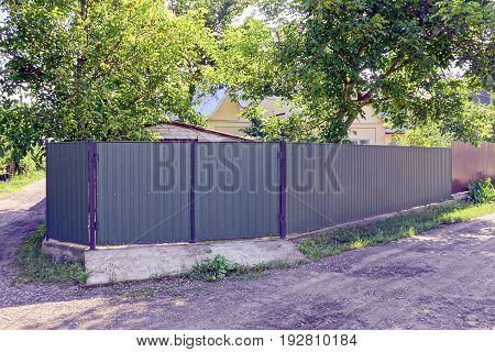A green fence and a gate in front of a rural road at the intersection