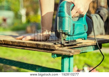 Carpenter saws plank in park with electric jig saw