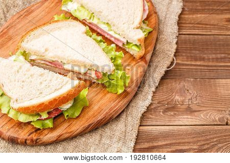 Photo of fresh burgers on wooden board at canvas fabric