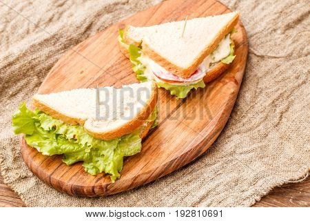 Photos fresh sandwich with greens and sausage on wooden board at linen cloth