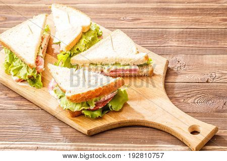 Image of bread with vegetables and sausage on wooden table