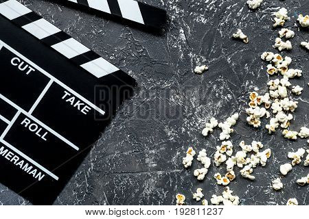 Watching the film. Movie clapperboard and popcorn on grey stone table background top view.