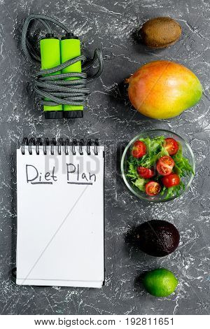 Slimming. Notebook for diet plan, fruits, salad and skipping rope on grey stone table top view mock up.