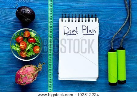 Tasty food for slimming. Notebook for diet plan, salad and fruits and measuring tape on white background top view mock up.