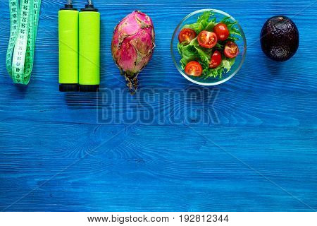 Slimming diet. Salad, fruits and measuring tape on blue wooden table top view copyspace.