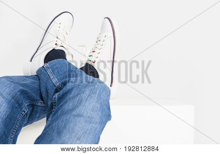 Closeup Shot of Mens Legs on White Fashion Sneakers and Jeans Laid on High Support.Horizontal Image