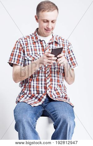 Youth Lifestyle Concepts and Ideas.Closeup Portrait of Caucasian Man with Handheld Cellphone Chatting While Sitting on White Box.Vertical Image Orientation