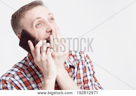 Youth Lifestyle Concepts and Ideas.Closeup Portrait of Surprised and Happy Caucasian Man Speaking on Cellphone. Posing Against White Background. Horizontal Image Orientation