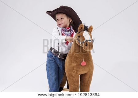 Little Children Consepts. Happy Smiling Caucasian Girl in Cowgirl Clothing Posing With Symbolic Plush Horse Against White. Horizontal Image Orientation