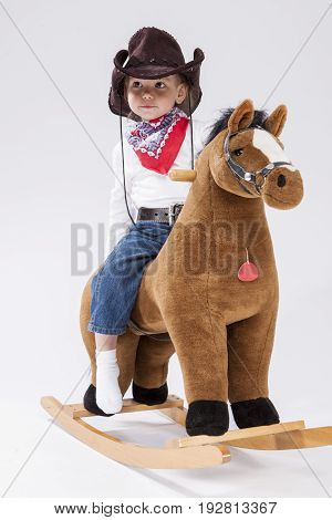 Little Children Consepts. Smiling Happy Little Caucasian Girl in Cowgirl Clothing Posing On Symbolic Horse Against White. Vertical Shot