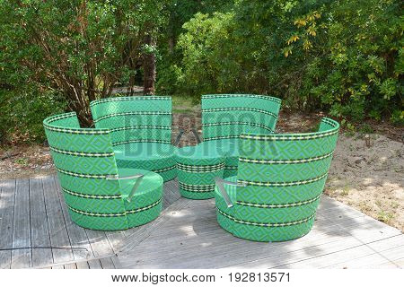 Comfortable green wicker chairs and table in a restaurant