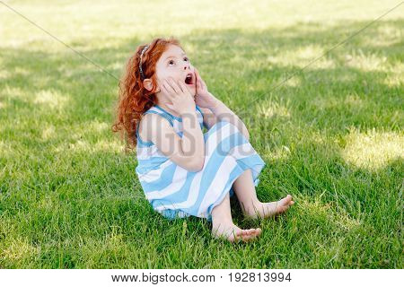Portrait of cute adorable surprised little red-haired Caucasian girl child in blue dress sitting on grass in park outside playing crying screaming in fear happy lifestyle childhood concept