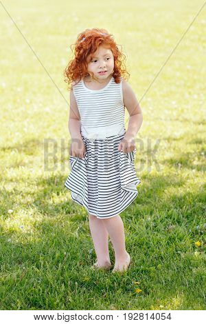 Portrait of cute adorable frightened little red-haired Caucasian girl child in white striped dress standing on grass in park outside crying screaming in fear lifestyle childhood concept
