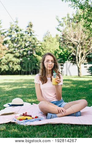 Portrait of young beautiful white Caucasian woman girl sitting on grass in park drinking fruit juice on summer daytoned with retro filters film effect rural country lifestyle