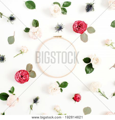 Embroidery frame with red and beige rose flower buds pattern on white background. Flat lay top view decorated concept.