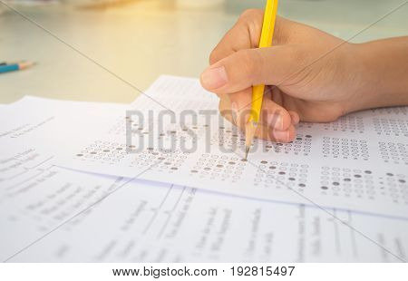 Asian student testing english exam or taking exercise on exams answer sheets with pencil in class room at school education concept