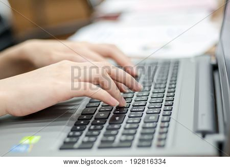 close up hand of business women use mouse pad and keyboard on laptop.