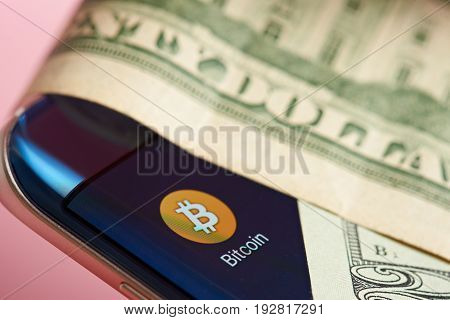 New york, USA - June 26, 2017: Bitcoin currency system on mobile application. Paper dollars on top of  bitcoin app