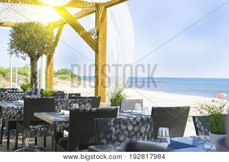 table and chairs in the restaurant on the blue sea background