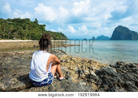 EL NIDO, PALAWAN, PHILIPPINES - MARCH 29, 2017: Woman looking the amazing view from the rocks at Las Cabanas Beach.