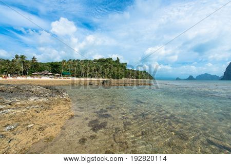 EL NIDO, PALAWAN, PHILIPPINES - MARCH 29, 2017: Clean water of Las Cabanas beach full of rocks