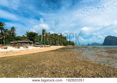 EL NIDO, PALAWAN, PHILIPPINES - MARCH 29, 2017: Wide angle view of Las Cabanas Beach with rocks palms and a restaurant beachfront
