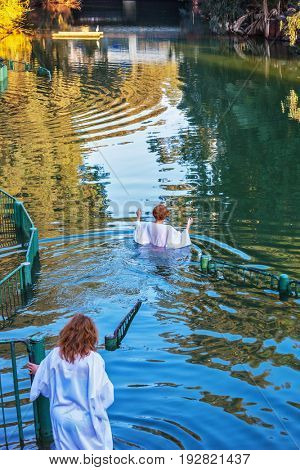 YARDENIT, ISRAEL - JANUARY 21, 2012: Christian pilgrims baptized in the Jordan River. They enter the water, dressed in special white robes