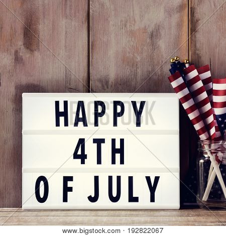 a lightbox with the text happy 4th of july and some american flags on a glass jar, on a rustic wooden background