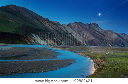 Night view to colorful mountain ridge and river flowing down in valley with sheep eating grass, Landmannalaugar, Iceland