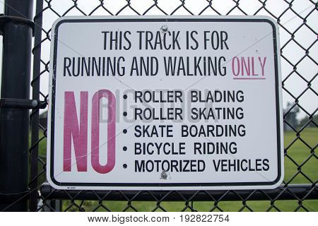 A sign on a fence at a local track reads that the track is for running and walking only. No Roller blading roller skating skate boarding bicycle riding motorized vehicles