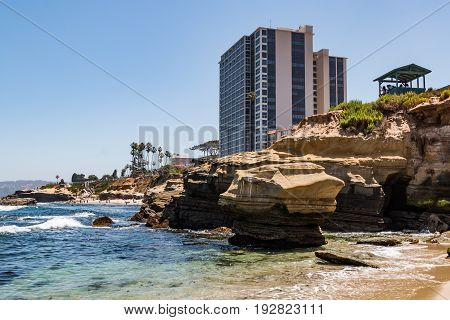 LA JOLLA, CALIFORNIA - JUNE 16, 2017:  Observation point overlooking the Children's Pool beach and natural sandstone rock formations, with surrounding hotels.