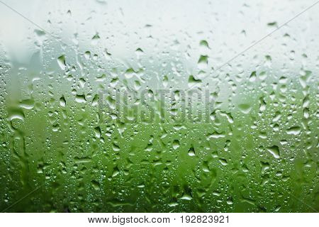 Water drops on the mirror when it rains with green background