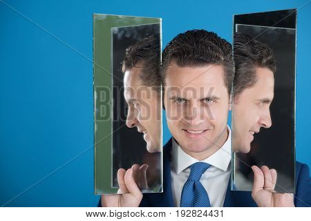 smiling man with beard and self reflection in mirror on blue background copy space
