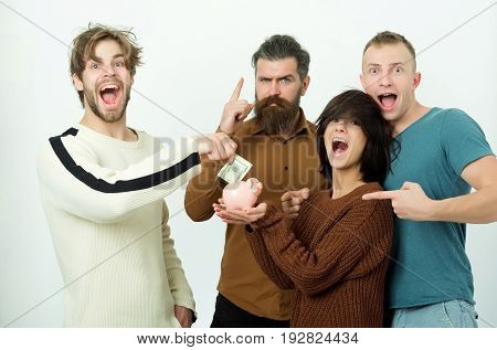 Happy friends or people adorable girl or cute woman and three men in casual wear putting dollars money in piggy bank with winning fists on white background. Savings budget finance and moneybox