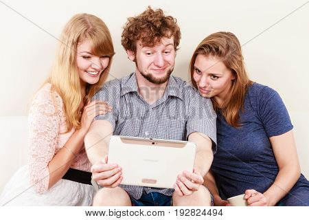 Friends browsing surfing internet on tablet. Young people man guy and women girls sitting on sofa relaxing at home.