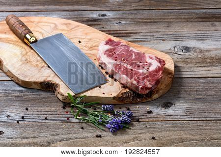 Large butcher knife and raw beef with marbled fat on carving board with spices and herbs