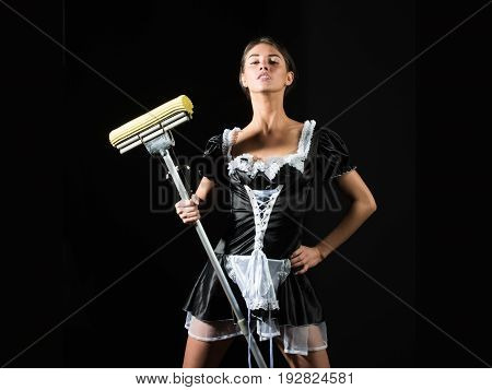 housemaid. pretty sexy girl or maid in uniform apron with mop on black background housekeeping and cleaning